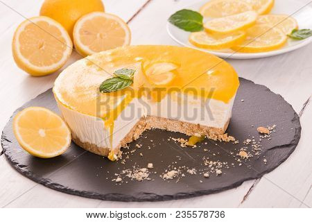 Lemon Cheesecake With Lemon Curd On Wooden Table.