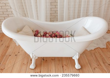 Bathtub Full Of Flowers In Minimalistic Interior With Brick Wall Background.