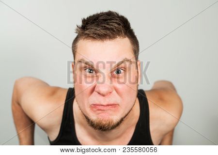 Young Funny Bearded Guy Dressed In Black Tank Top Sitting On The Toilet On Gray Background.