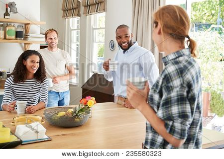 Four young adult friends having coffee in the kitchen