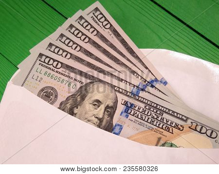 Envelope With Us Dollars On The Green Wooden Table. Money In Envelope
