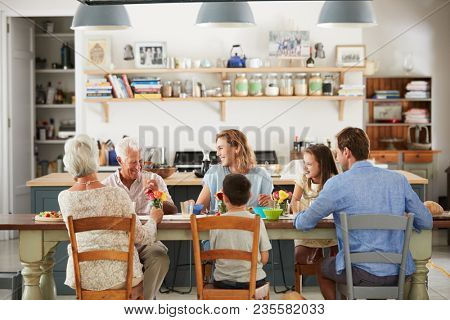 Three generation family eating in the kitchen at home