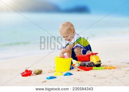 Baby With Toy Boat In Swimming Pool. Little Boy Learning To Swim In Outdoor Pool Of Tropical Resort.