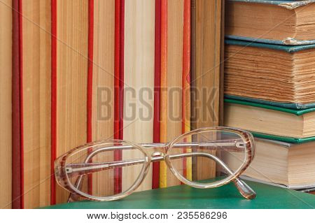 Glasses And Many Old Hardback Books On Wooden Shelf. Education Background. Library Concept