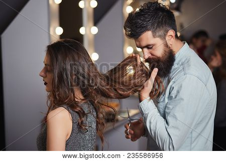 Handsome Man Hairdresser Smelling Hair Of A Beautiful Girl In Elegant Evening Dress. Cute Male Haird