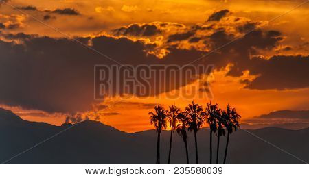 A Beautiful View Of An Orange Sunrise In The Sky With High Palm Trees On The Foreground And Mountain