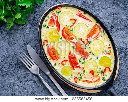 Pan With Traditional Italian Frittata On Dark Gray Stone Table, Forks, Parsley, Pepper, Tomatoes. Sc