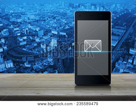 Email Icon On Modern Smart Phone Screen On Wooden Table Over City Tower, Street And Expressway, Busi