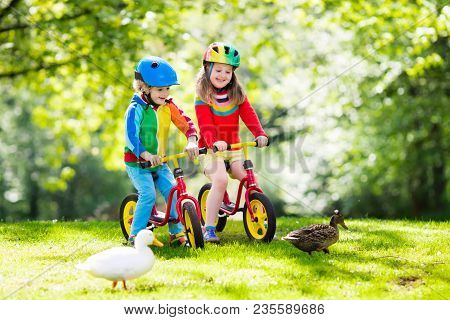 Child Riding Bike. Kid On Bicycle In Sunny Park. Mother Teaching Little Girl To Cycle. Preschooler L