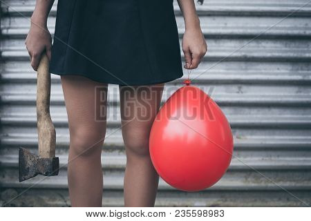Teenage Girl Standing Near A Wall With Balloon And Axe In Her Hands.