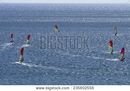 Seven Windsurfers Are Riding On The Surface Of The Dazzling Beautiful  Mediterranean Sea On Cape Pra