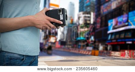 Composite image of mid section of photographer holding vintage camera
