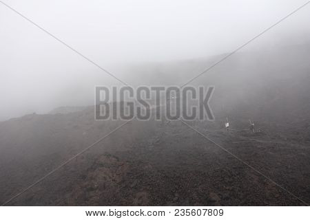 The Etna Volcano. Black Volcanic Earth And Thick Fog On Mount Etna. Place For Text. The Island Of Si