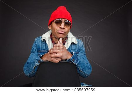 Black Guy In Stylish Outfit Of Denim And Sunglasses Sitting On Chair And Looking At Camera In Disbel