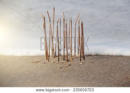 Incense Stick And Smoke From Incense Burning. Incense Stick Burning On The Beach, Against The Backgr