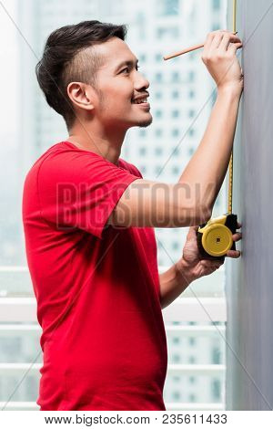 Young indonesian man sizing with tape measure in skyscraper building