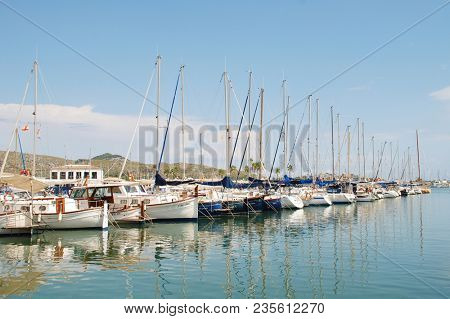 MAJORCA, SPAIN - SEPTEMBER 4, 2017: Sailing boats moored in the marina at Puerto Pollensa on the Spanish island of Majorca. The seaside destination is the most Northerly town on the island.
