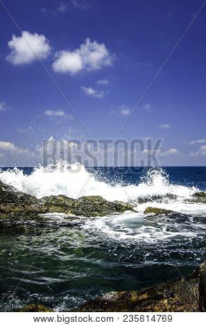 Soft Wave Hitting The Rock At The Shoreline With Cloudy And Blue Sky Background