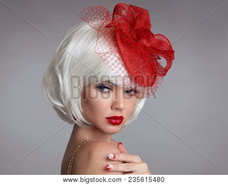 Christmas Makeup. Red Lips Make-up. Beautiful Blond Closeup Portrait In Red Hat. White Short Bob Hai