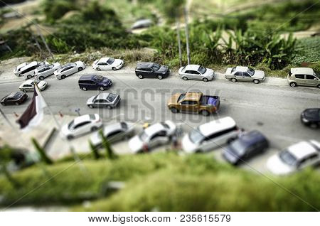Tilt Shift Effect From Aerial View, Group Of Car Park At Garden. Hill And Cloudy Sky Background