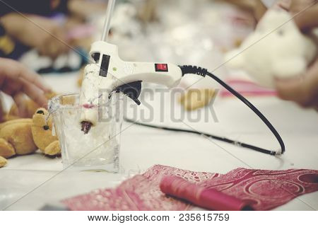 Hot Stick Glue Gun On Cup. Red Fabrick And Doll On White Table. Blur Background