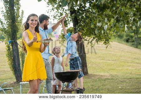 Beautiful woman, mother of two children, smiling and showing thumbs up while spending quality time with her happy family at BBQ in summer