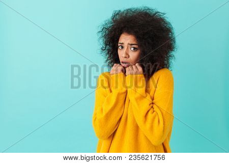 Image closeup of scared woman with shaggy hair pressing arms in fear or offense isolated over blue background