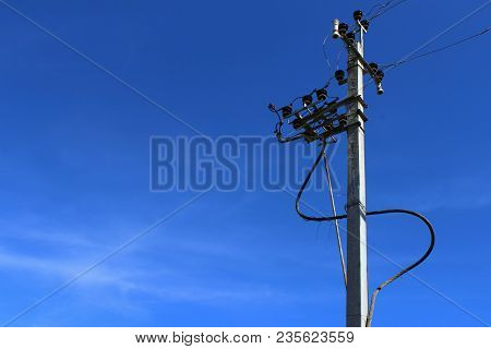 High Voltage Electricity Pillars Cables On Electricity Power Tower On Blue Sky Background. Transmiss