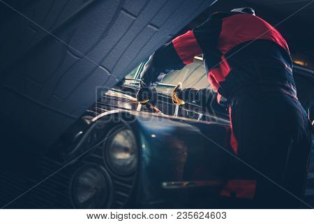 Classic Car Restoration Fix. Caucasian Men Passionate About Vintage Vehicles Trying To Fix Some Issues with His American Classic Car Gasoline Engine. poster