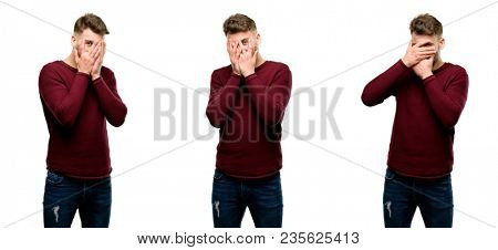 Handsome blond man smiling having shy look peeking through her fingers, covering face with hands looking confusedly broadly isolated over white background