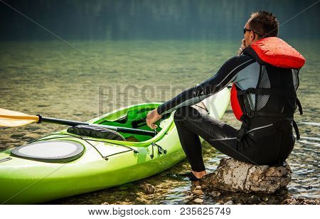 Tour Kayaker And The Lake. Caucasian Men In His 30s And His Green Plastic Kayak. Water Recreation Th