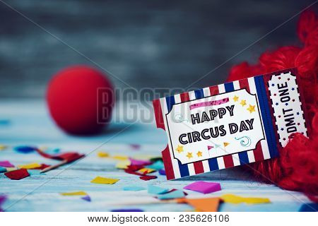 a curly red hair wig, a red clown nose and the text happy circus day in a simulated admission ticket, on a blue rustic wooden surface full of confetti