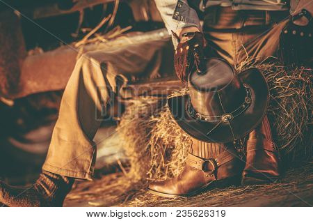 Caucasian Western Wearing American Cowboy Taking Rest Inside His Barn. Cowboy Leather Shoes And Hat.