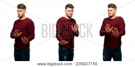 Handsome blond man annoyed with bad attitude making stop sign with hand, saying no, expressing security, defense or restriction, maybe pushing isolated over white background