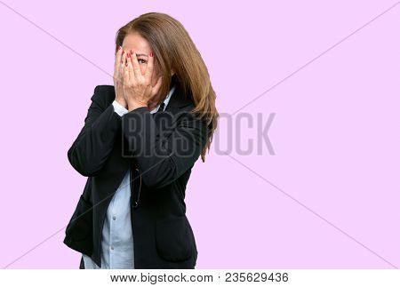 Middle age business woman smiling having shy look peeking through her fingers, covering face with hands looking confusedly broadly