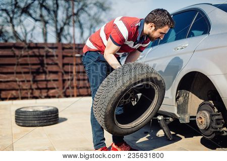 Changing A Flat Car Tire In The Backyard. Tire Maintenance, Damaged Car Tyre Or Changing Seasonal Ti