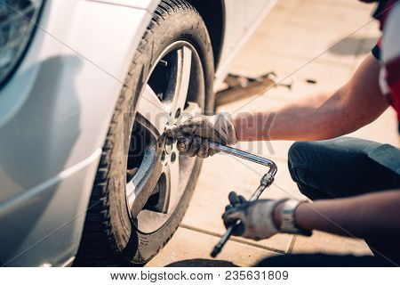 Tire Maintenance, Damaged Car Tyre Or Changing Seasonal Tires Using Wrench. Changing A Flat Car Tire