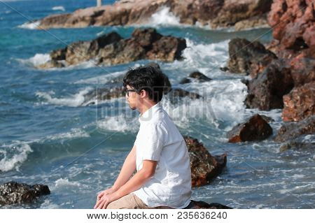 Lonely Depressed Young Asian Man With Casual Clothes Sitting On The Rock Of Sea Shore.