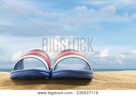 Close Up Blue Sandals On Sand Of Beach On Blur Beautiful Sky Background, Summer Concept