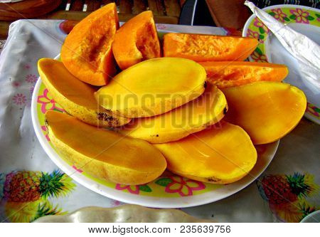 Ripe Mango And Papaya Slices Slices Of Ripe Mango And Papaya Heaped In A Small Flowered Plate