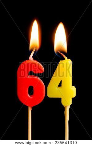 Burning Candles In The Form Of 64 Sixty Four (numbers, Dates) For Cake Isolated On Black Background.