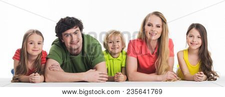 Happy smiling family of two parents and three children lying on the floor studio isolated on white background