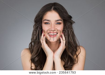 Beautiful smiling young woman stroking her clean beauty face