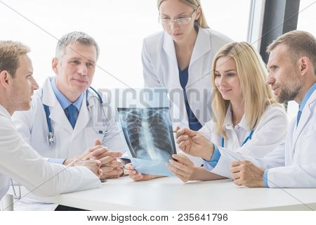 Healthcare, medical and radiology concept - group of doctors looking at x-ray