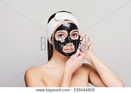 Skin Care. Portrait Of Young Girl Peeling Off Black Mask From Her Face. Purifying Spa Treatment, Whi