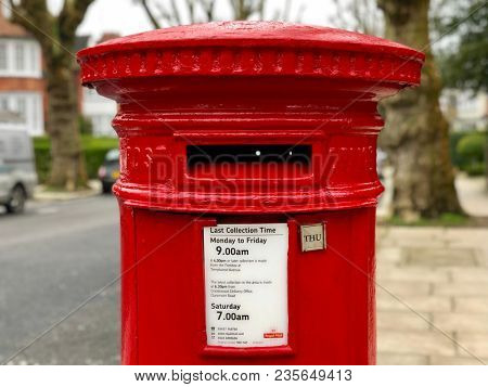 LONDON - APRIL 11, 2018: A distinctive Royal Mail red post box on a resident street in Camden, North London, UK.