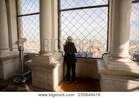 Venice, Italy - October 26, 2017: Woman on observation deck St. Mark's Campanile watching on Venice Panorama. Italy.