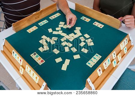 Turkish Board Game Okey (rummikub). A Table With Green Cloth And Chips. Hands Of The Players.