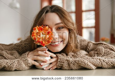 Beautiful portrait of brunette woman 20s in sweater resting in cafe and smiling ttwhile holding one flower in hands poster