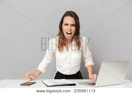 Portrait of a furious young business woman sitting at the office desk and yelling isolated over white background